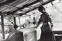 Photo of Dorothea Mitchell operating large, circular lumber saw