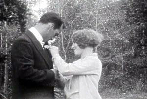 Photo of Dolly Dearborn pinning the flower on Jack Madison, in The Fatal Flower